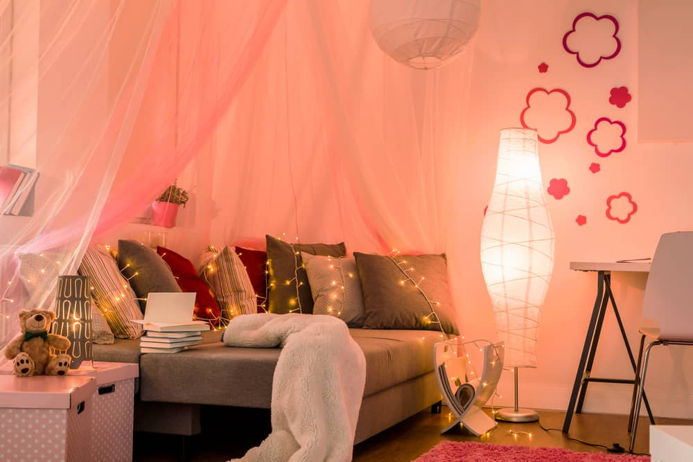 Stylish lighted girl's bedroom with comfortable sofa
