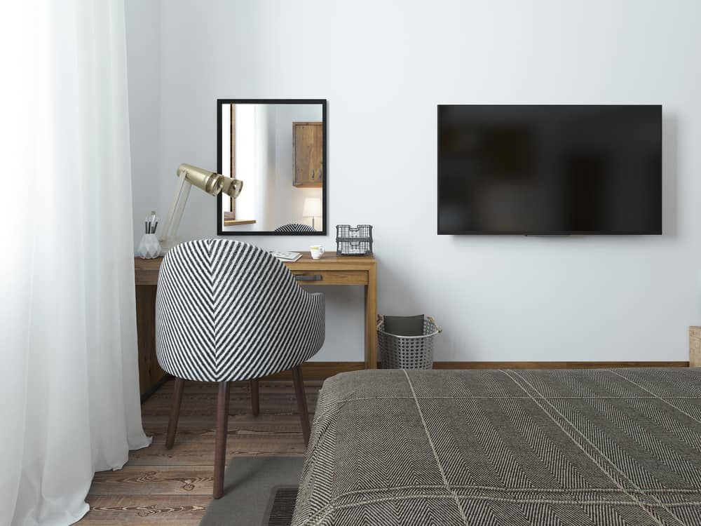 TV hanging on a wall in a bedroom